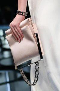 Sacoche rose pâle avec une anse métallique et une anse en chaîne